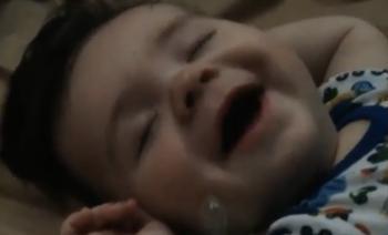 Slaperige-baby-giechelt-zichzelf-wakker