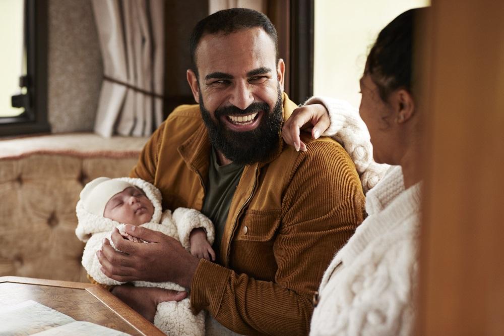 lachende vader met baby en moeder op bank in zwangerschapsverlof