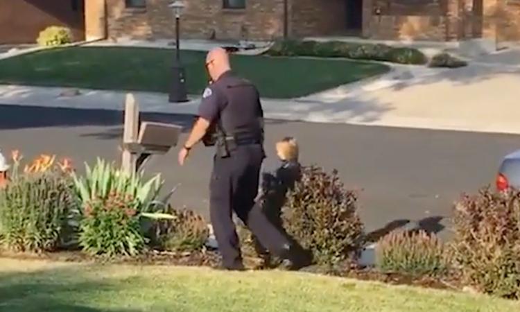 Politieagent helpt meisje met de omgeving checken op monsters
