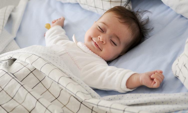 Dit is de reden dat je baby met z'n armen omhoog slaapt