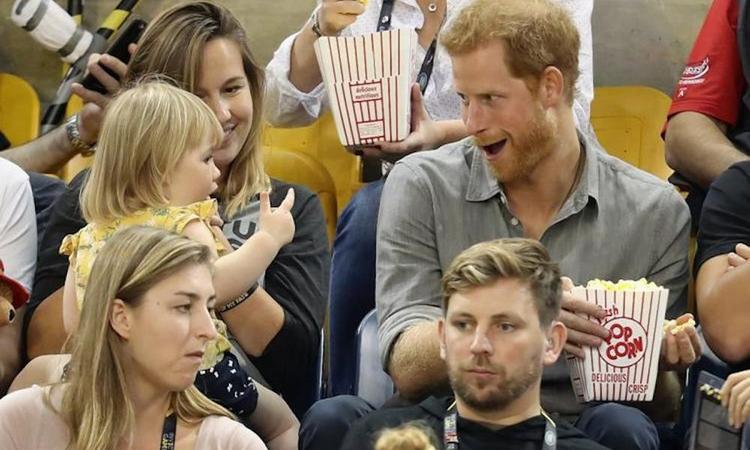 Meisje pikt popcorn van prins Harry