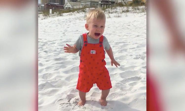 Peuter voelt voor de eerste keer zand onder zijn voeten